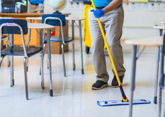 Man dry mopping a classroom floor with chairs and desks organized in the room